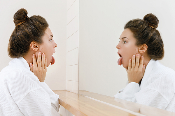 Woman looking on her tongue in the mirror Photograph by Privetik