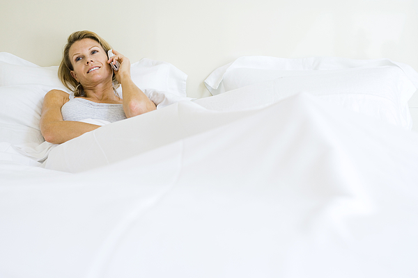 Woman lying in bed, talking on cell phone, looking away Photograph by PhotoAlto/Frederic Cirou