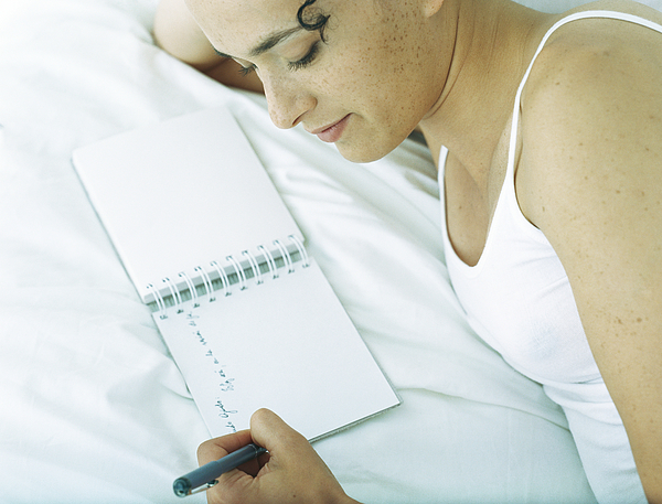 Woman lying on side on bed writing in notebook with pen Photograph by Laurence Mouton