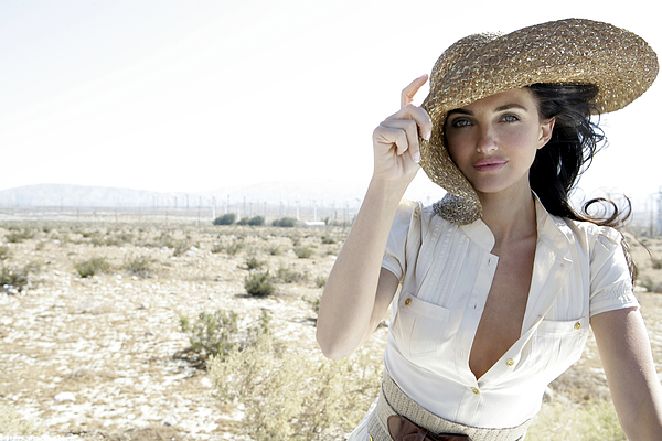 Woman outdoors holding large hat Photograph by Eye Candy Images