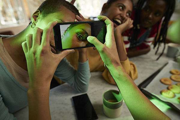Woman photographing female friends eye on phone Photograph by Klaus Vedfelt