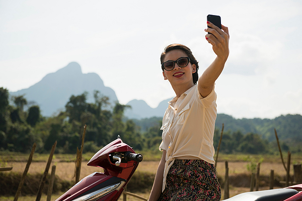 Woman photographing self on moped, Vang Vieng, Laos Photograph by Ben Pipe Photography