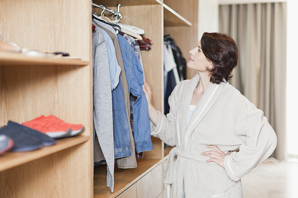 Woman picking clothes out of closet Photograph by Hybrid Images