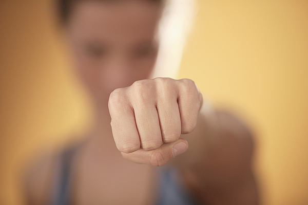 Woman punching Photograph by Comstock