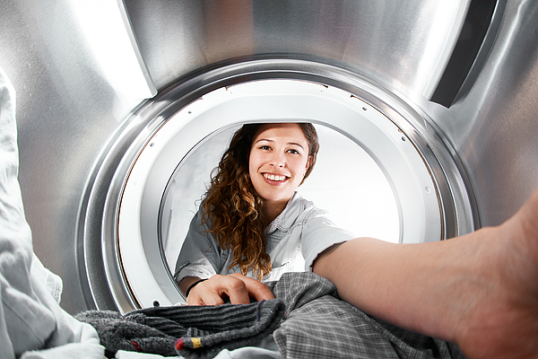 Woman reaching into tumble dryer, seen from inside Photograph by RapidEye