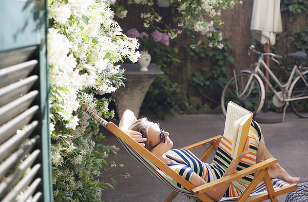 Woman relaxing on deck chair in backyard, reading a book Photograph by Kathrin Ziegler
