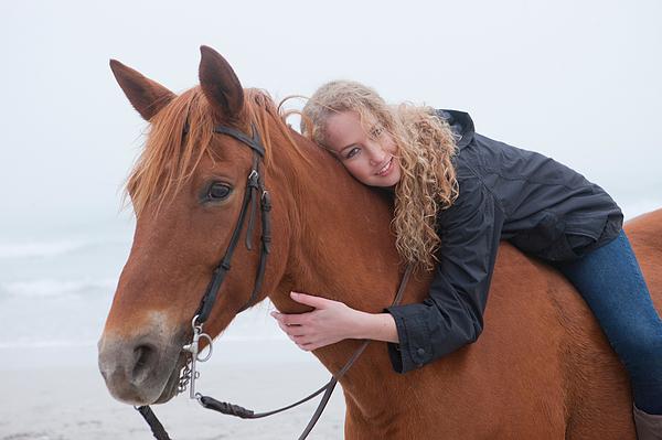 Woman riding horse on beach Photograph by Zero Creatives