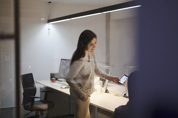 Woman sharing idea on smart phone with coworker in office Photograph by FangXiaNuo