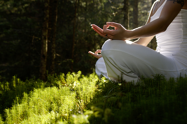 Woman sitting in meditating position outdoors, low angle view Photograph by Westend61 - Hans Huber