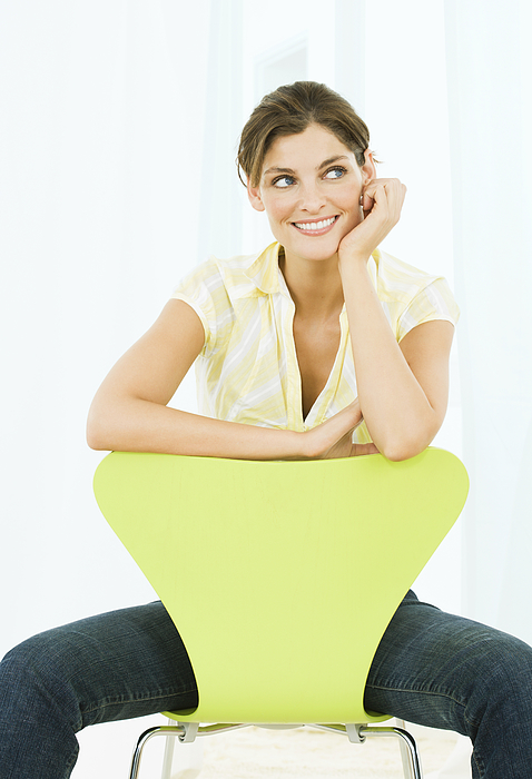 Woman sitting on chair, head on hand, smiling Photograph by Pando Hall