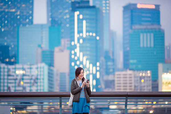 Woman smiling while using smartphone in city Photograph by D3sign