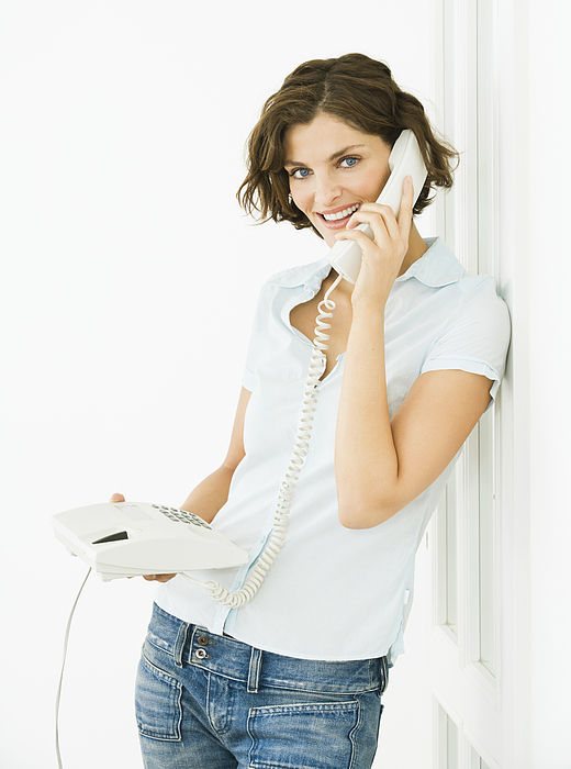 Woman standing at a door, using telephone, smiling Photograph by Pando Hall