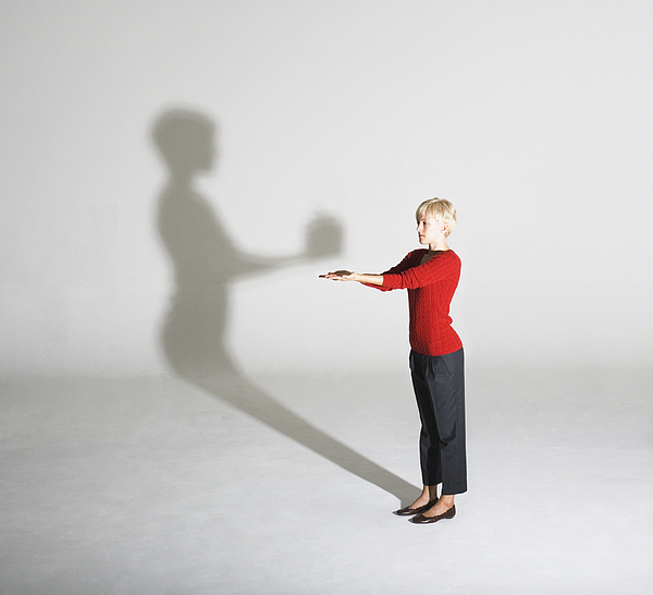 Woman standing with her shadow giving her a gift Photograph by Martin Barraud