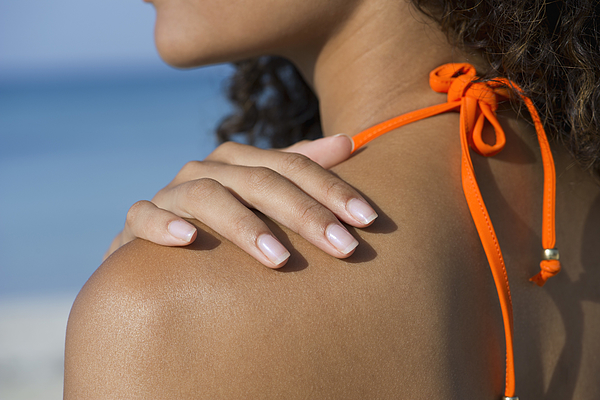 Woman touching bare shoulder at the beach, cropped Photograph by PhotoAlto/Frederic Cirou