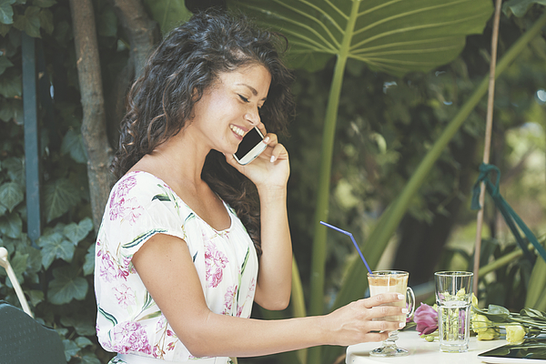 Woman using cell phone in sunny garden Photograph by Fotostorm