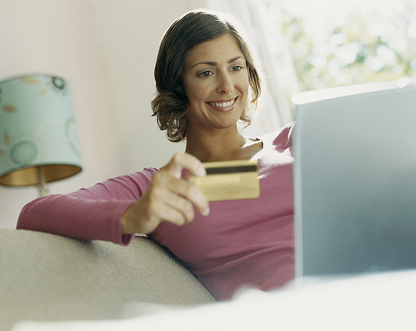 Woman Using Her Bank Card Online With a Laptop Photograph by Digital Vision.