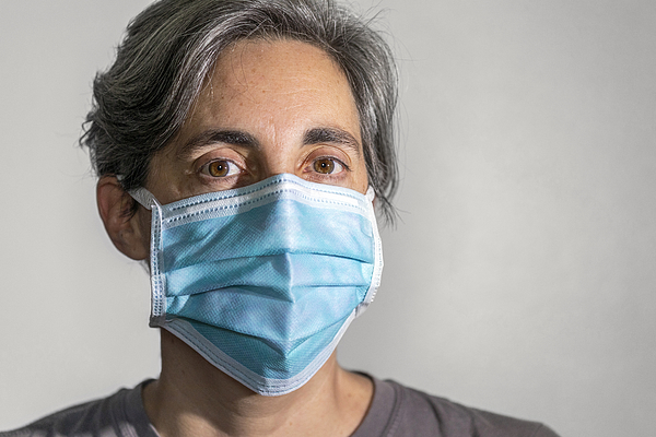 Woman wearing a surgical mask, protective face mask against infectious diseases like coronavirus and influenza Photograph by Andrew Merry