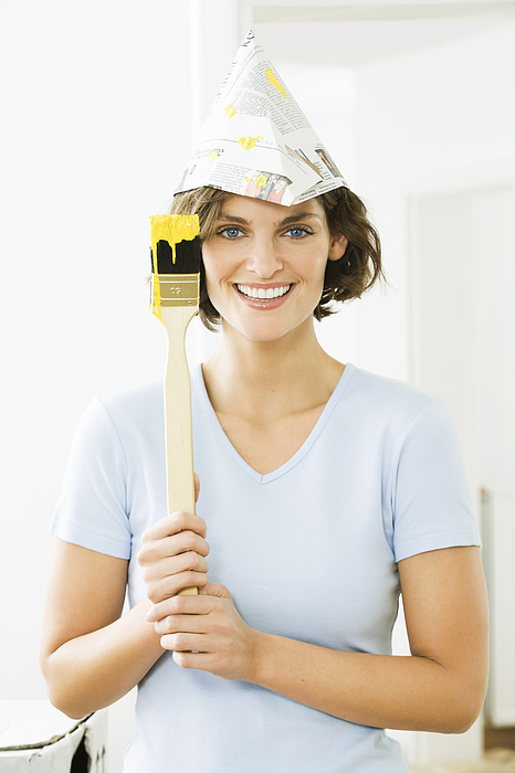 Woman wearing newspaper hat with paintbrush Photograph by Pando Hall