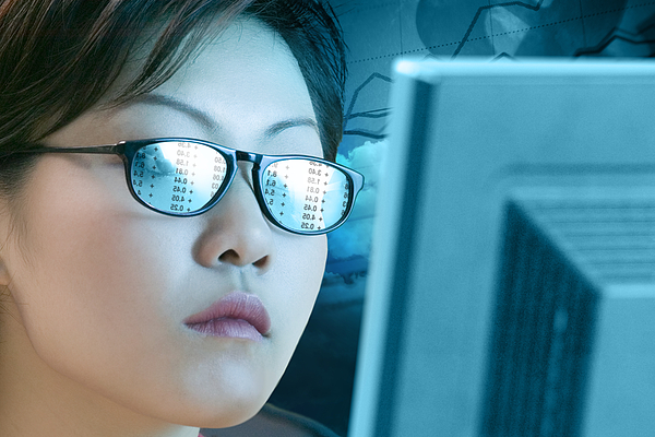 Woman with a reflection off a computer in her glasses Photograph by Comstock Images