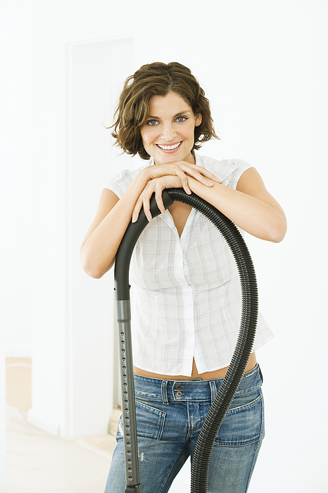 Woman with a vacuum cleaner, smiling Photograph by Pando Hall