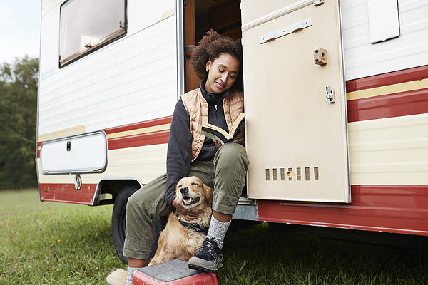 Woman with dog reading book in motor van Photograph by Klaus Vedfelt