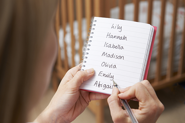 Woman Writing Possible Names For Baby Girl In Nursery Photograph by MachineHeadz