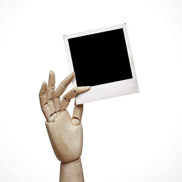 Wood hand with instant photo frame Photograph by Sfio Cracho
