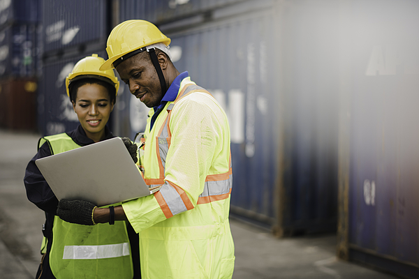 Young African american men and woman worker Check and control loading freight Containers by use computer laptop at commercial shipping dock felling happy. Cargo freight ship import export concept Photograph by Niphon Khiawprommas