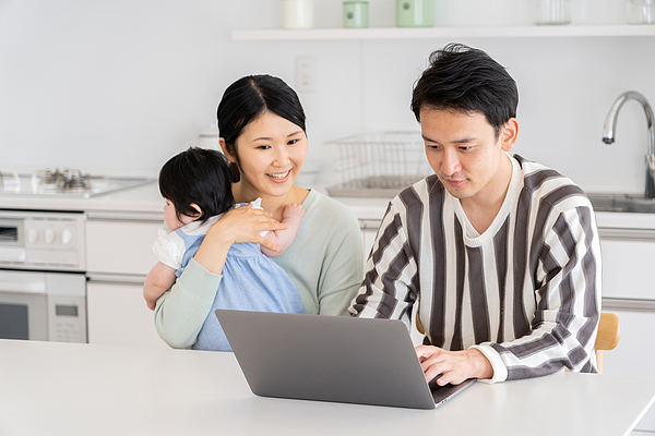 Young Asian Family Using Laptop In Kitchen Photograph by Itakayuki