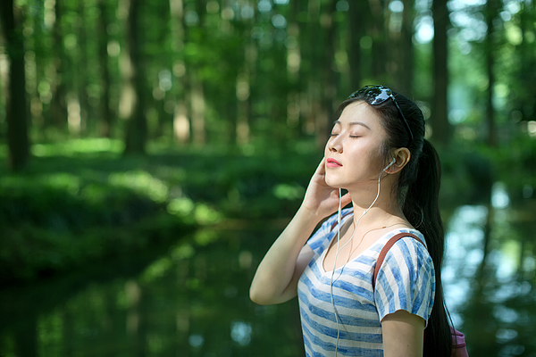 Young asian woman listening to music in forest,with eyes closed Photograph by Xia Yuan