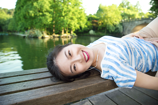 Young asian woman lying on pier above lake,listening to music Photograph by Xia Yuan