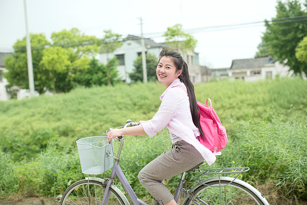 Young asian woman riding bicycle through country rapeseed field Photograph by Xia Yuan
