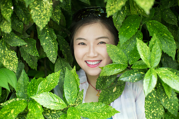 Young asian woman standing behind green leaves Photograph by Xia Yuan