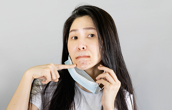 Young Asian woman wearing medical face mask and white t shirt. isolated on gray background,health care concept Photograph by Patchanan Promunat