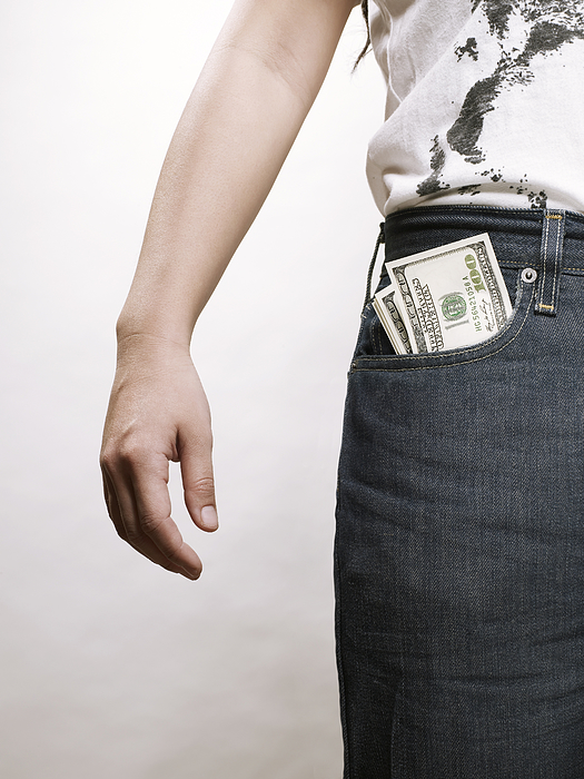 Young asian woman with dollar bills in pocket Photograph by Ballyscanlon