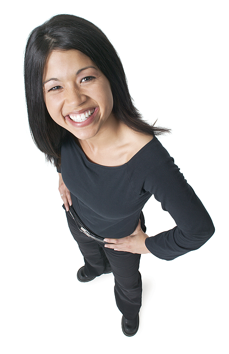 Young Attractive Asian Woman Dressed In Black Puts Her Hands On Her Hips And Smiles Up To The Camera Photograph by Photodisc