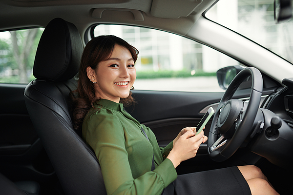 Young beautiful woman using smartphone while driving car Photograph by Makidotvn