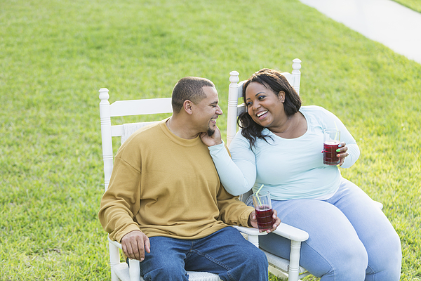 Young Black Couple Sitting, Talking, Drinking Photograph by Kali9