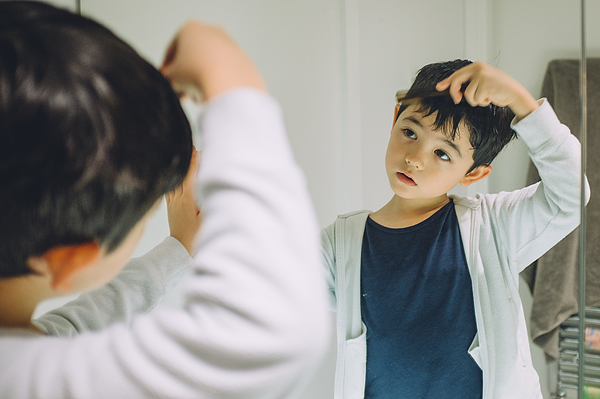 Young boy getting ready to go out. Photograph by © Peter Lourenco