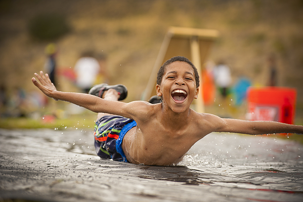 Young Boy Splashing Down On A Slip N Slide Photograph by Stephen Simpson