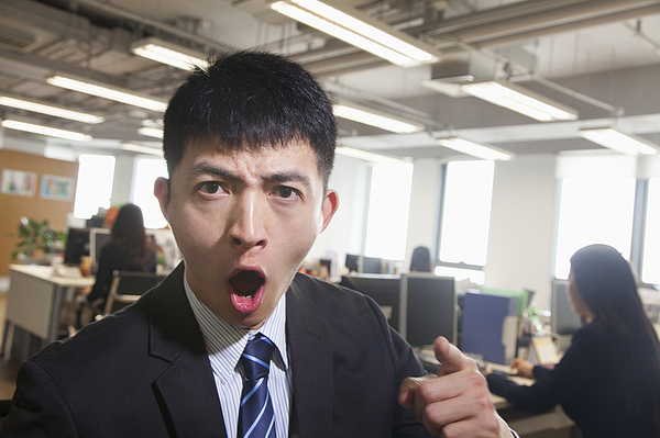 Young Businessman pointing and shouting, looking at camera Photograph by XiXinXing