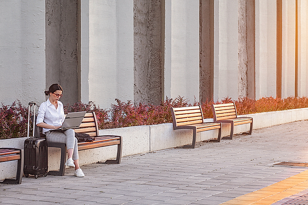 Young Businesswoman Working On A A Laptop While Sitting On A Bench On The City Street Photograph by Gruizza