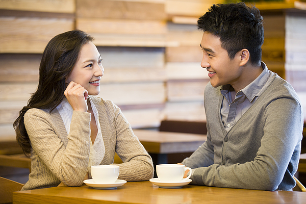 Young couple chatting in cafe Photograph by BJI / Blue Jean Images