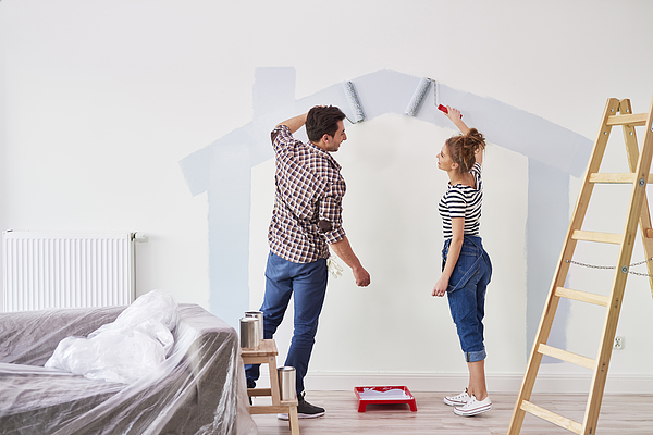 Young couple painting the interior wall in their new apartment Photograph by Gpointstudio
