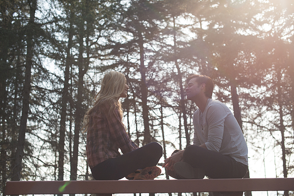 Young couple sit on bench in woods Photograph by Christopher Malcolm