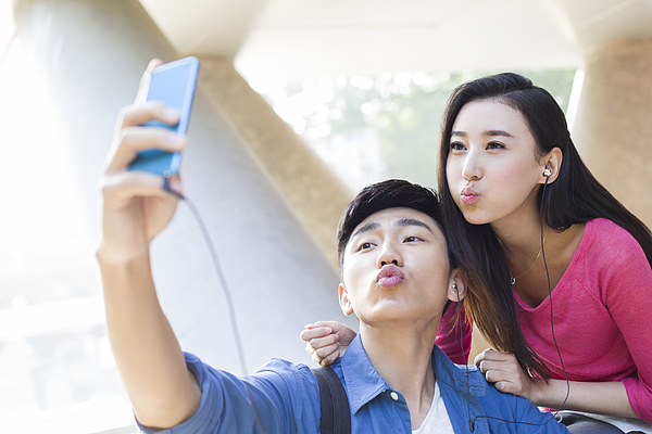 Young couple taking self portrait with a smart phone Photograph by Lane Oatey / Blue Jean Images
