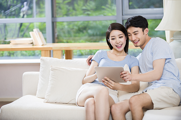 Young couple using digital tablet on sofa Photograph by BJI / Blue Jean Images