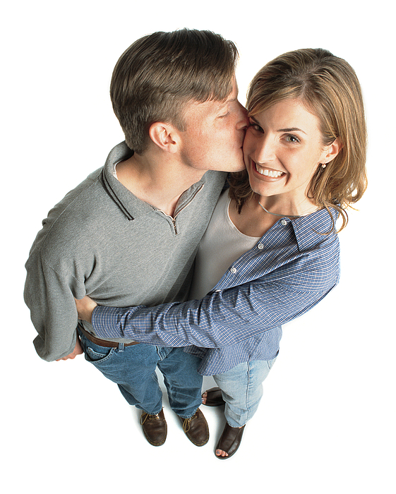 Young Couple With Brown Hair With The Boy Kissing The Girl On The Cheek And She Is Excited And Smiles Photograph by Photodisc