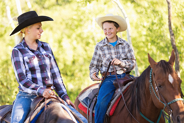 Young cowboy and cowgirl riding horses during trail ride Photograph by SDI Productions