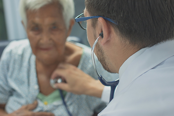 Young doctor listening heartbeat with stethoscope of old woman,Rural medicine concept. Photograph by Visoot Uthairam